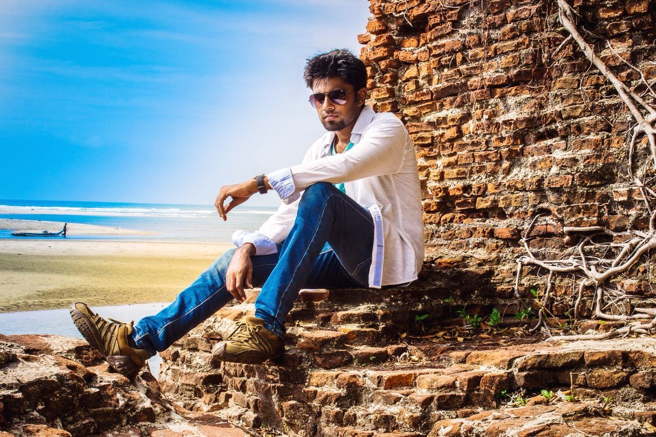 Handsome Man In Sunglass Posing By Brick Wall At Alamparai Fort
