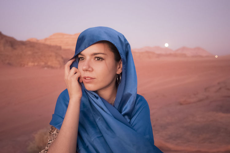 Young woman wearing headscarf while standing at desert