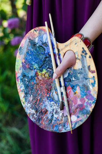 Midsection of woman holding palette and paintbrushes