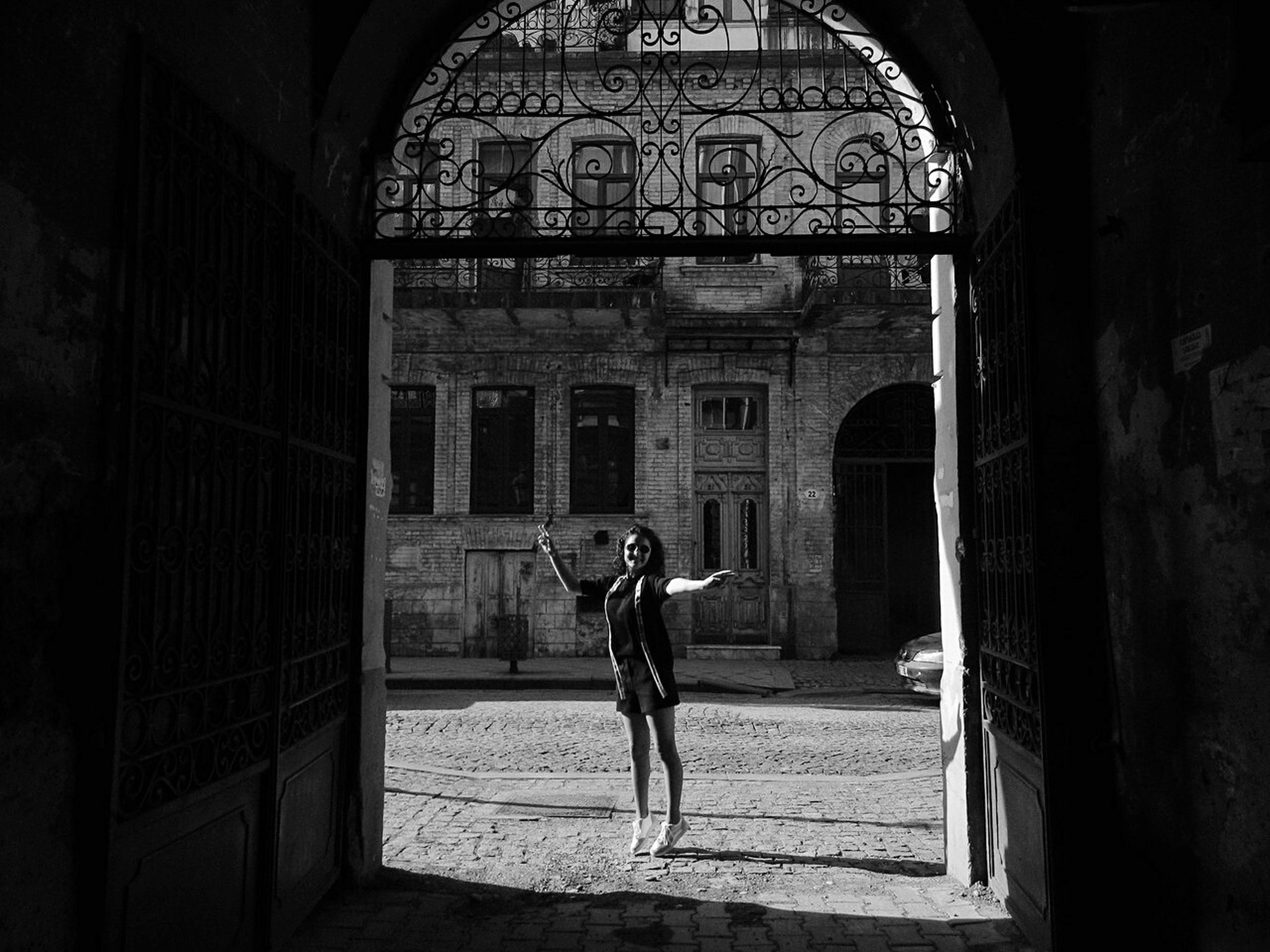 architecture, built structure, real people, one person, lifestyles, full length, building, building exterior, leisure activity, the past, history, arch, day, standing, men, tourism, old, women, architectural column, deterioration