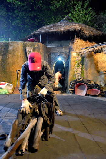 Making kiln-fired charcoal is a traditional handicraft industry. Charcoal Kilns In The Dark Industry Tradition Adult Adults Only Black Burn Wood Charcoal Day Economic Full Length Give Headwear Helmet Kiln Labor Force Lifestyles Men Motorcycle One Person Outdoors People Real People Sitting Tree
