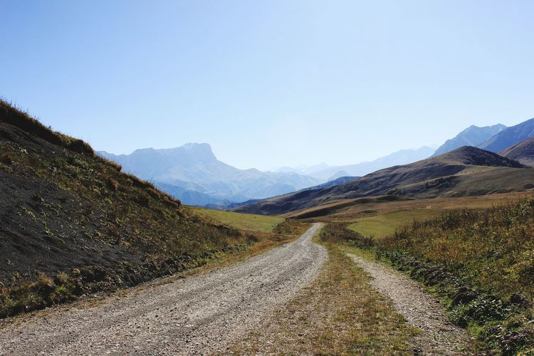 Dirt road by mountains against clear sky