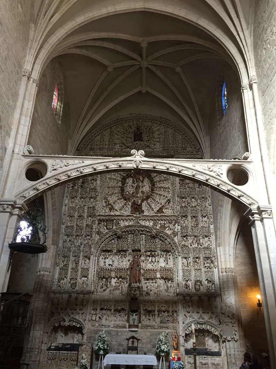 religion, place of worship, spirituality, arch, architecture, indoors, built structure, statue, pew, sculpture, cross, altar, low angle view, no people, day