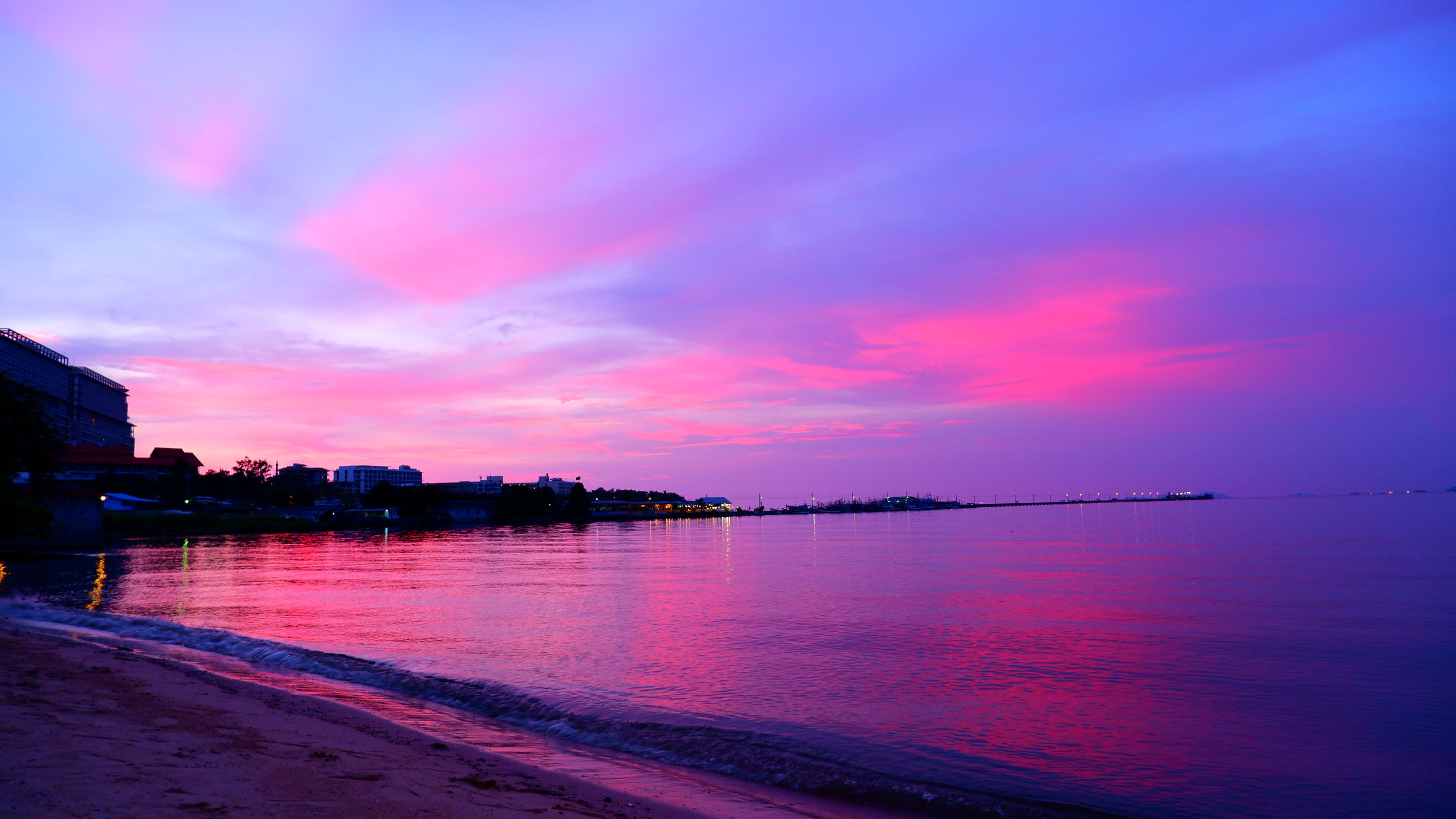 water, sky, sea, sunrise, dawn, horizon, cloud, beauty in nature, beach, scenics - nature, reflection, nature, architecture, afterglow, ocean, land, morning, tranquility, travel destinations, city, built structure, pink, tranquil scene, no people, coast, landscape, outdoors, multi colored, purple, building exterior, travel, idyllic, dramatic sky, environment, building, magenta, sunlight, blue, holiday
