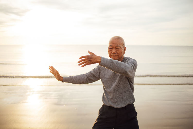 Senior man exercising while standing at beach against sky during sunset