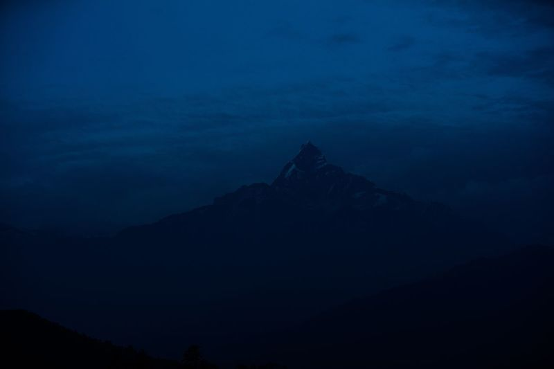 Low angle view of silhouette mountains against sky at night