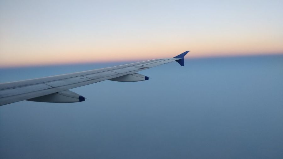 Airplane wing against clear sky during sunset