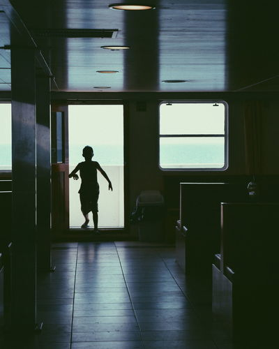 One Person Real People Window Full Length Indoors  Leisure Activity Lifestyles Men Standing Day Glass - Material Rear View Transparent Flooring Transportation Mode Of Transportation Walking Ferryboat Sillouette Interior Shadows & Lights