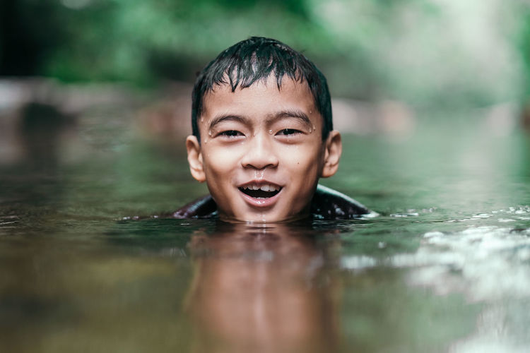 Portrait of happy boy swimming in lake at forest