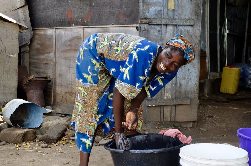Cheerful woman washing clothes against house