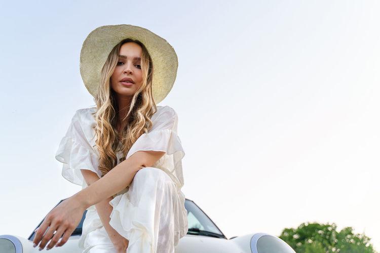 Portrait of woman in hat against sky