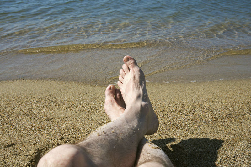 Low section of man relaxing on beach