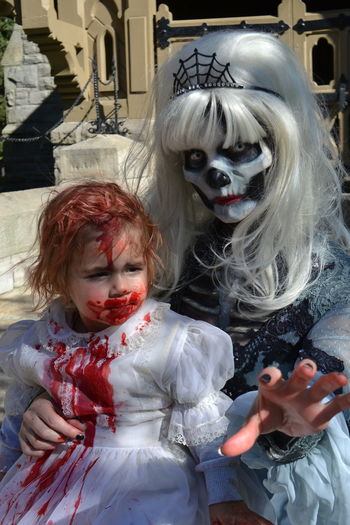 Portrait of woman holding girl with spooky make-up during halloween