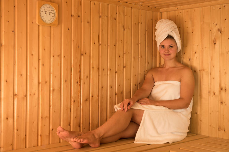 Beautiful young woman relaxing in sauna