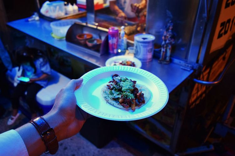Cropped image of man holding taco in plate at food stall