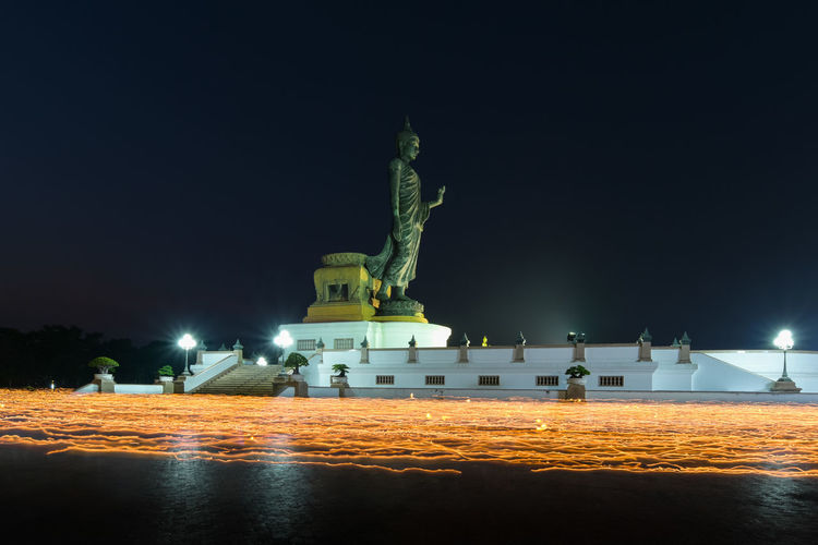 Statue in illuminated city at night