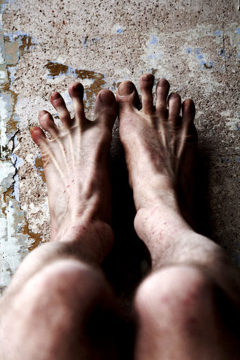 Low Section Of Man Spreading Toes On Weathered Wall