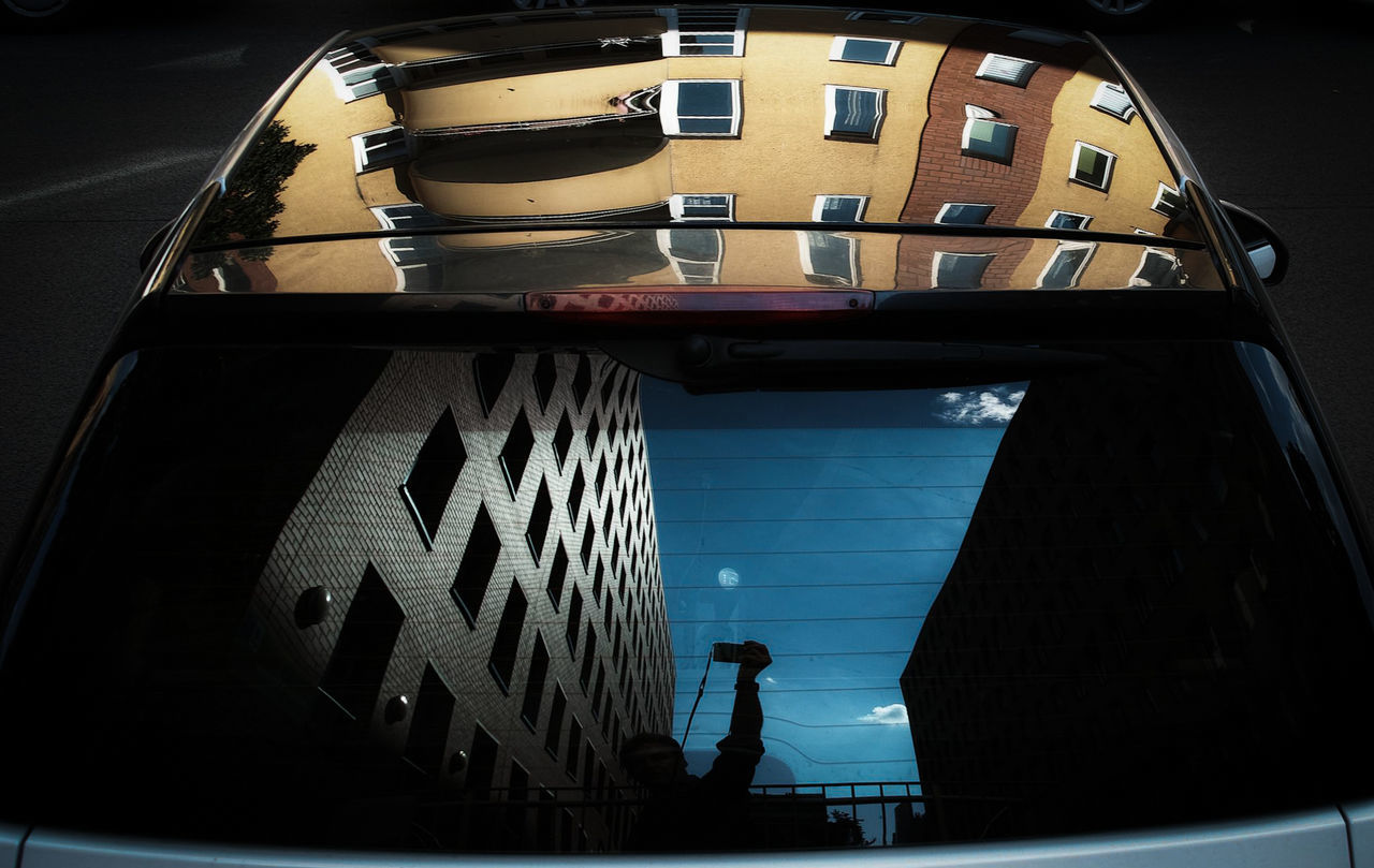 Man with arms raised reflecting on car rear windshield