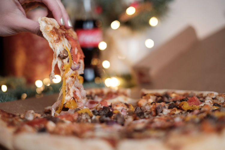 Female hand holding yummy slice of pizza Human Body Part Food And Drink Slice Of Pizza Pizza Body Part Christmas Unrecognizable Person Close-up Selective Focus Food Human Hand Freshness Finger Preparation  Food Porn Fast Food Yummy Christmas Lights Human Finger One Person Hand Light Indoors  Temptation Real People