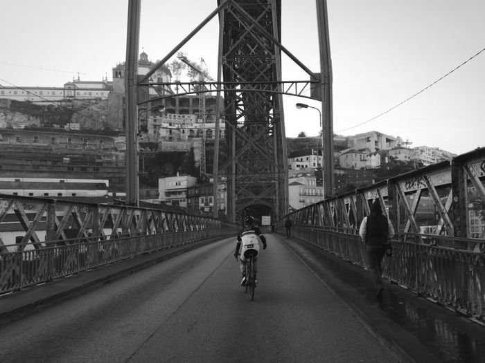 Rear view of people riding bicycle on bridge in city
