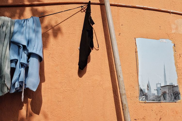 Low angle view of clothes drying on clothesline against wall