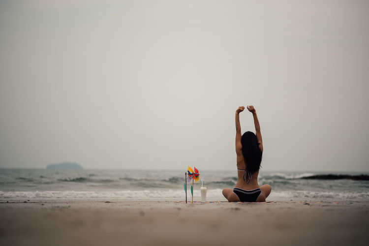 Beach Sea Land Sky Healthy Lifestyle Horizon Water Rear View One Person Arms Raised Exercising Lifestyles Leisure Activity Horizon Over Water Human Arm Sand Nature Beauty In Nature Wellbeing Outdoors Human Limb