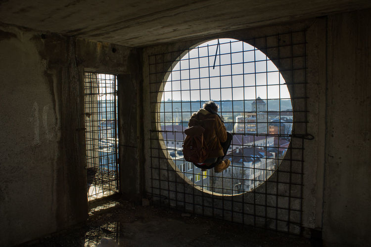 Rear View Of Man Hanging On Circular Window Against Sky