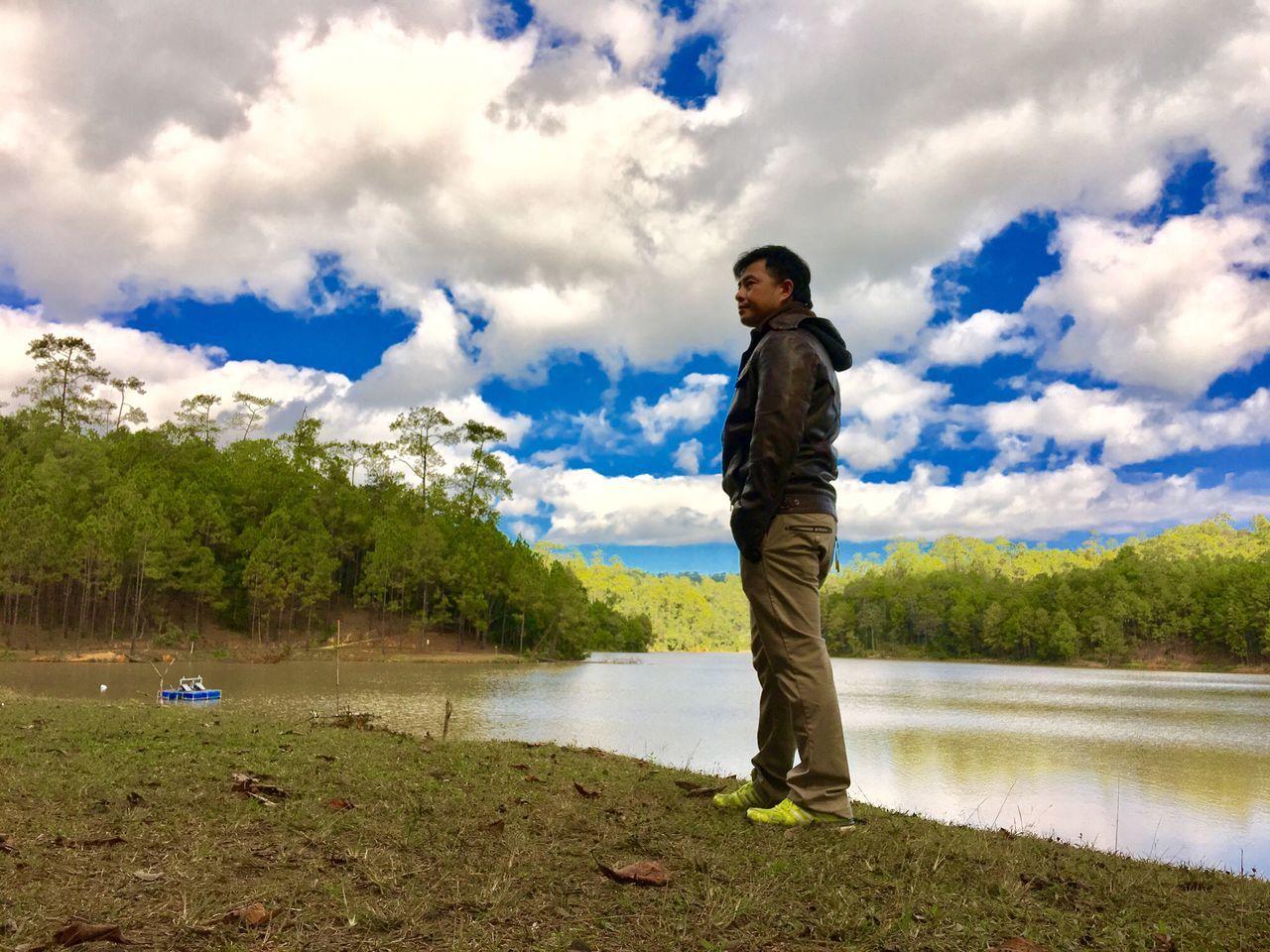 Man Standing At Lakeshore Against Sky