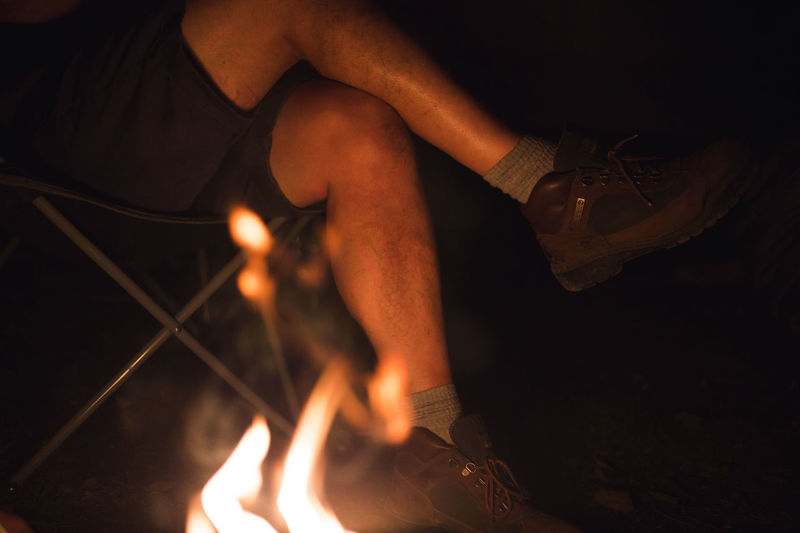 Camper sits by bright fire burning in campsite wearing hiking / walking boots and shorts at night Flames Hiking Relaxed Atmosphere Ambience Atmospheric Burning Camper Crossed Legs Explorer Flame Heat - Temperature Hiker Hiking Boots Human Body Part Leisure Activity Lifestyles Low Section Man's Legs Night Outdoors People Real People Togetherness Two People Walking Boots