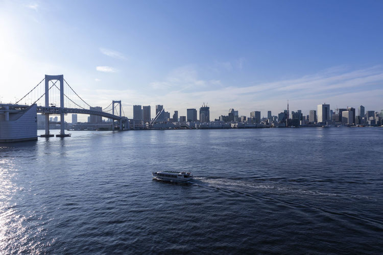 View of suspension bridge in city across tokyo bay.