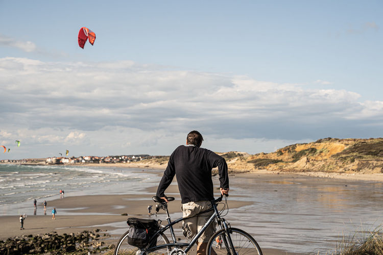 Man with bicycle on beach against sky