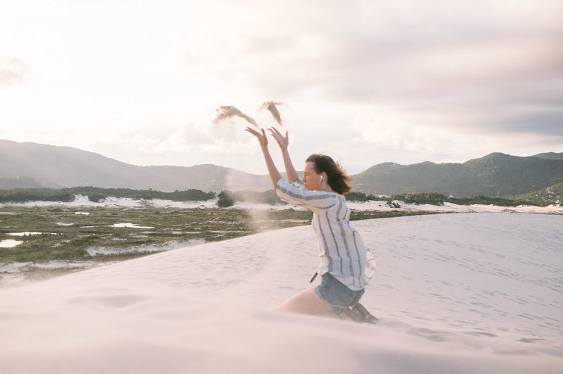 Side view of woman throwing sand while kneeling at beach