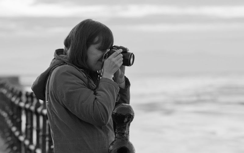 Side view of woman photographing sea against cloudy sky