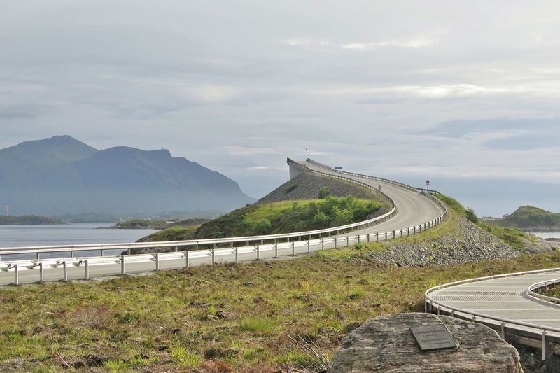 Low angle view of road against sea and mountains