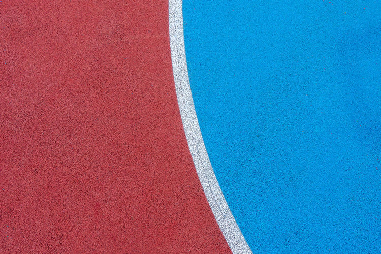 Colorful sports court background. top view to red and blue field rubber ground with  lines outdoors.
