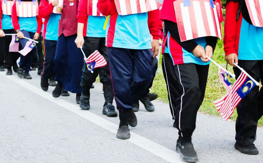 Low section of marching band holding malaysian flag