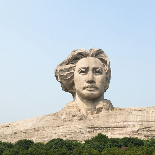Low angle view of youth mao zedong statue against clear sky