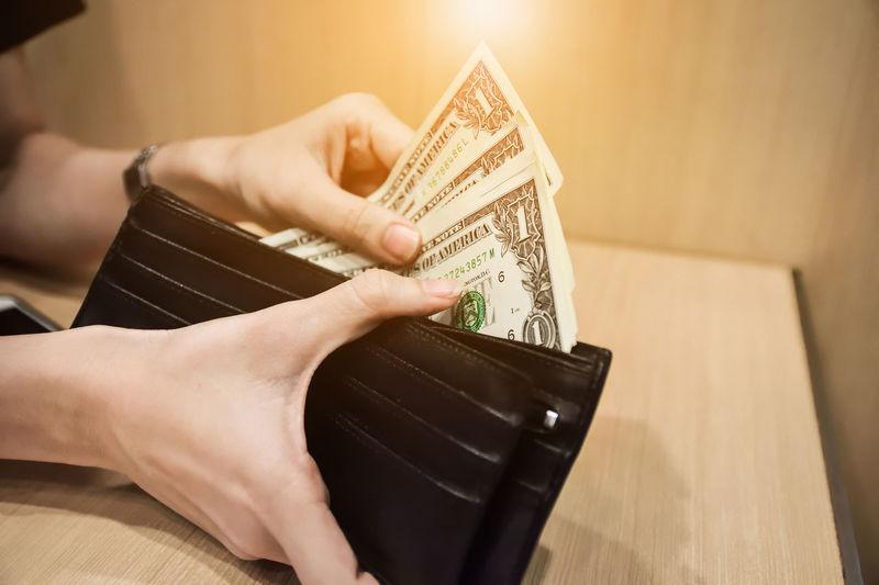 Close-up of woman holding dollar bills