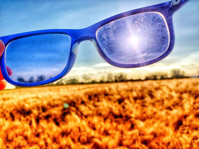 Close-up of sunglasses on field against sky