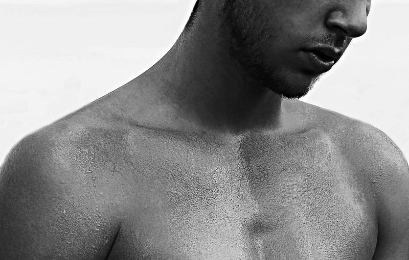Close-Up Of Shirtless Man Against White Background