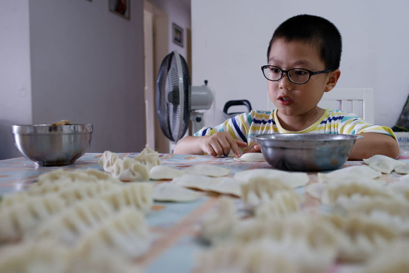 Boy Making Dumplings On Table At Home