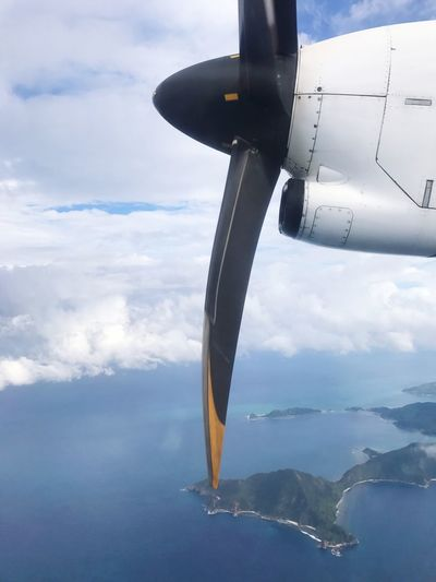 Close-up of airplane flying over sea against sky