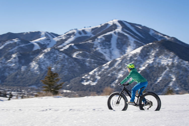 Bicycle on snowcapped mountain against clear sky