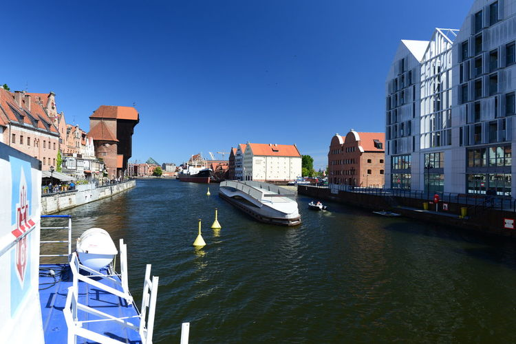 Boats in canal amidst buildings against clear sky