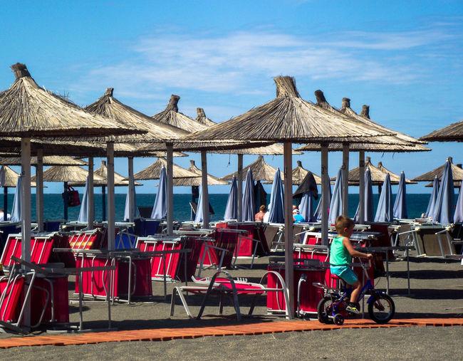 Summertime Summer Views Sandy Beaches Beachphotography Kid Riding Bike Red Color Beach Sky Beach Umbrella Sun Lounger Lounge Chair Resort Parasol Sunshade Outdoor Chair
