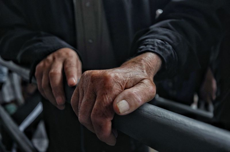 Cropped image of hands holding railing