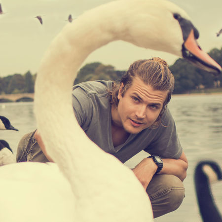 Beak Nature Swans Bird Birds Casual Clothing Day Flying Lake Leisure Activity Lifestyles Looking At Camera One Person Outdoors People Portrait Real People Sky Swan Transportation Water Wildlife Young Adult Young Men Young Women