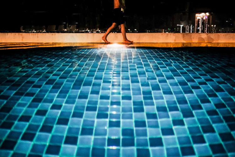 Low section of man walking on swimming pool