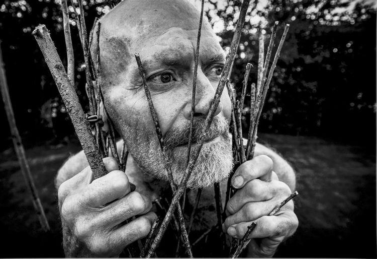 Close-up of mature man holding sticks