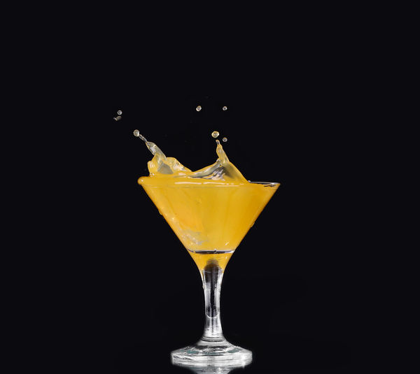 Close-up of drink on glass against black background
